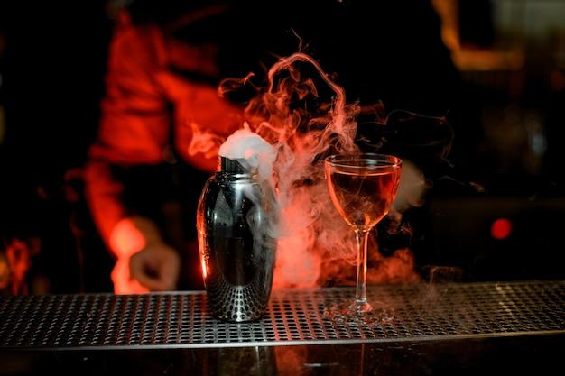 Barista in piedi in primo piano di cocktail nel bicchiere e shaker in acciaio fumoso