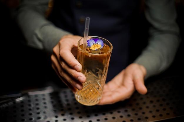 Barista in possesso di un dolce cocktail alcolico decorato con un fiore
