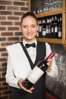 Barista in possesso di una bottiglia di vino