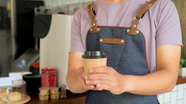 Barista in possesso di una tazza di caffè da asporto inviare ai clienti.