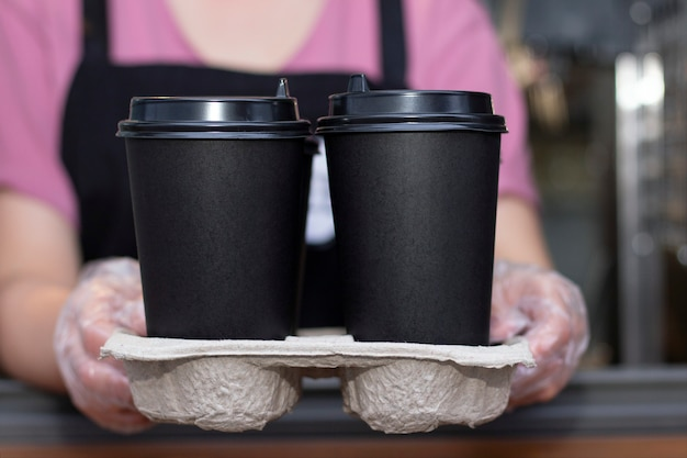 Barista in un grembiule tiene il caffè caldo in una tazza di carta in mano. prelievo al negozio di caffè.