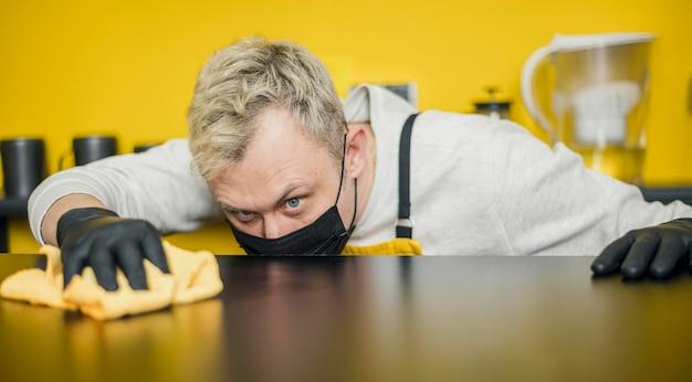Barista maschio con maschera medica e guanti pulizia tavolo