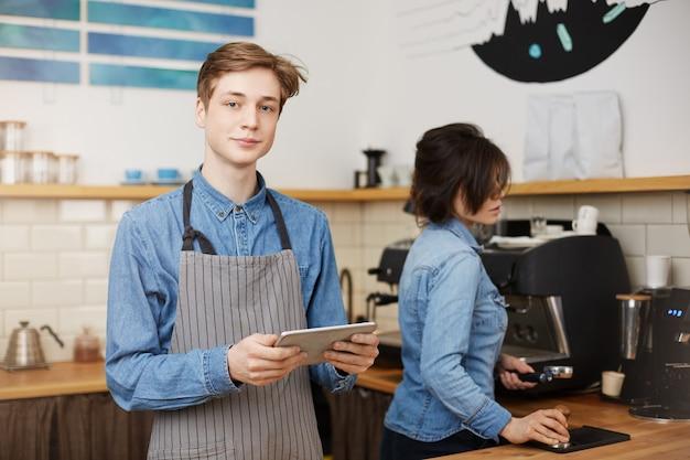 Barista maschio prendendo ordine, tenendo la linguetta, barista femmina fare il caffè
