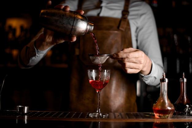 Barista maschio professionista che versa una bevanda alcolica rossa dall'agitatore d'acciaio attraverso il setaccio