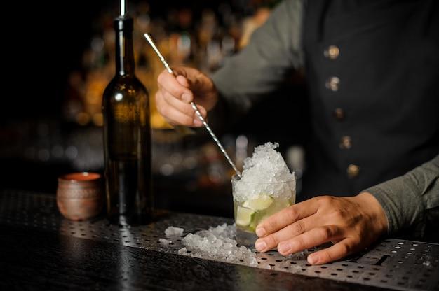 Barista mescolando cachaca con lime e ghiaccio, rendendo il cocktail caipirinha