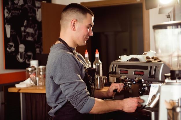 Barista professionista che tiene il latte scaldavivande in metallo utilizzando la macchina da caffè.