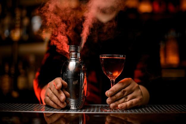 Barista professionista che tiene un cocktail nel bicchiere e shaker fumoso