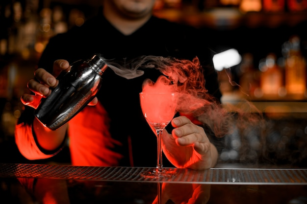 Barista professionista che versa un fumo nel bicchiere da cocktail dallo shaker