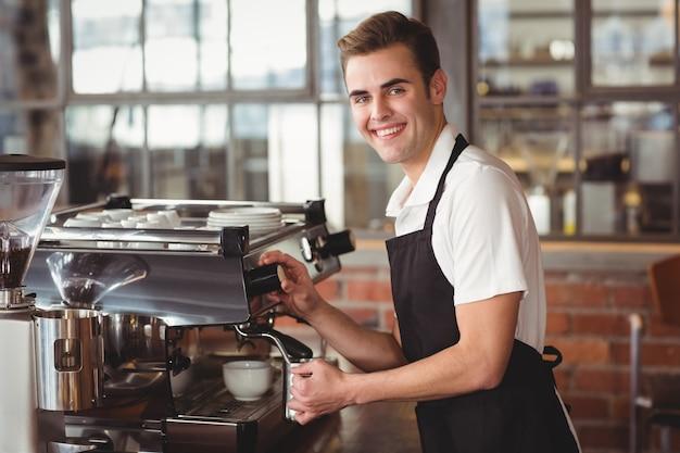 Barista sorridente che cuoce a vapore latte alla macchina del caffè
