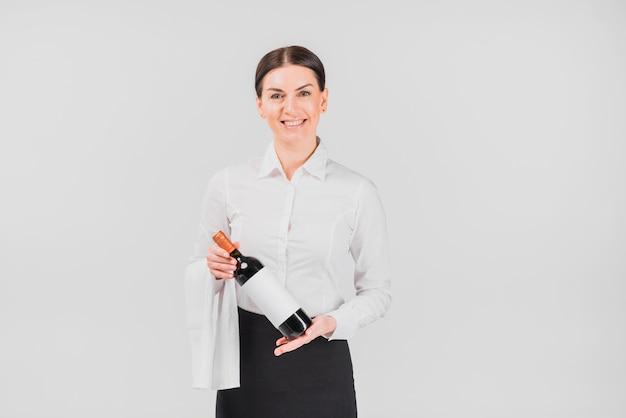 Barista sorridente e offrendo una bottiglia di vino