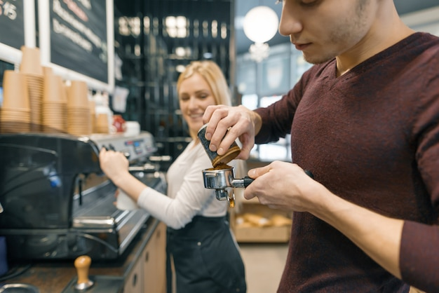 Barista uomo e donna che fanno caffè, coppia di giovani che lavorano in caffetteria.