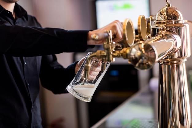 Barista versando birra dal rubinetto nel bicchiere di pinta