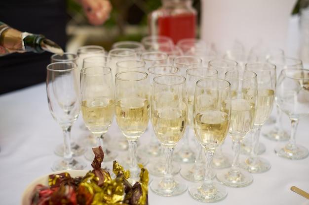 Barista versando champagne o vino in bicchieri da vino sul tavolo durante la cerimonia di nozze