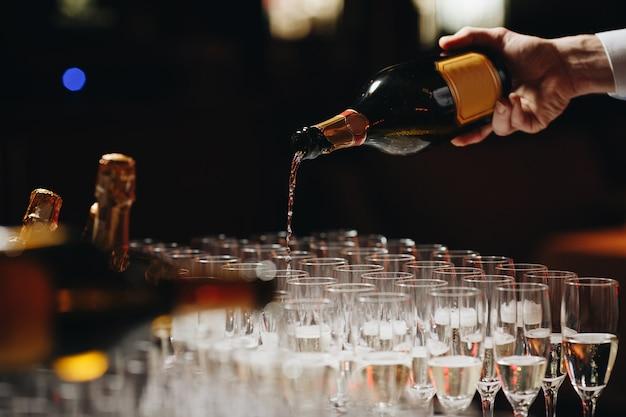 Barista versando champagne o vino in bicchieri di vino sul tavolo durante la solenne cerimonia di nozze all'aperto