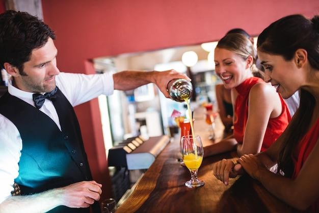 Barista versando cocktail in vetro al bancone del bar