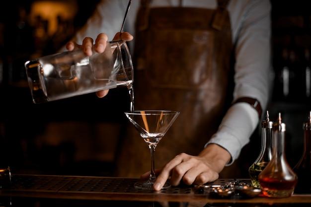 Barista versando una bevanda alcolica dal misurino al bicchiere da martini