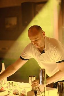 Barman aggiungendo ingredienti cocktail su cocktail di whisky sul bancone bar