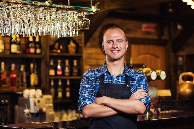 Barman al lavoro nel pub, ritratto di allegro lavoratore barista in piedi, cameriere che offre menu, un pub.bar.restaurant.classic.evening.ristorante europeo. bar europeo. ristorante americano. bar americano.