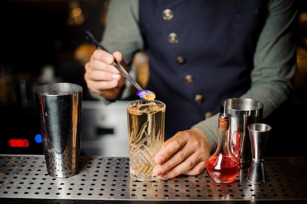 Barman che decora un dolce cocktail alcolico con un fiore