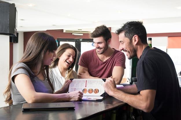 Barman che mostra il menu ai clienti al bancone del bar