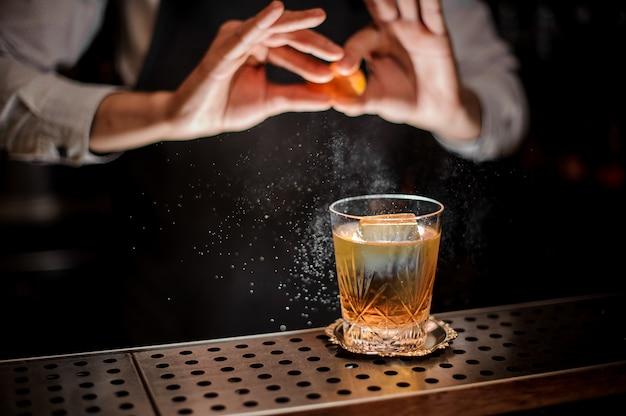 Barman che produce un gustoso cocktail estivo vecchio stile con succo d'arancia