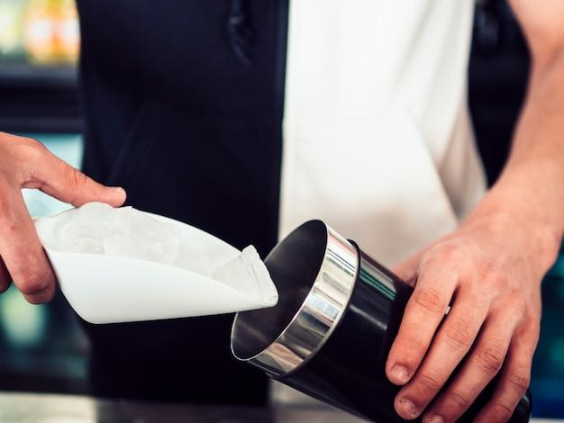 Barman che riempie shaker con ghiaccio