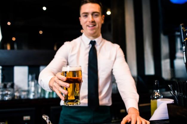 Barman che serve una pinta di birra in un bar