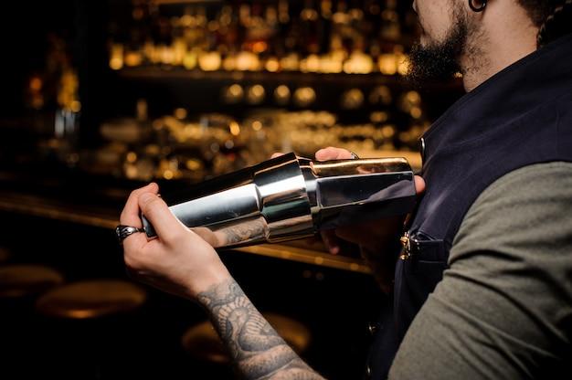 Barman con barba e tatuaggio sulla sua mano facendo cocktail estivo in shaker