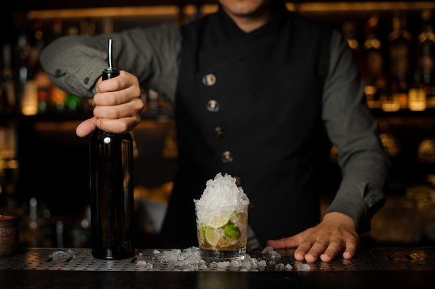 Barman con in mano una bottiglia di cachaca per preparare il cocktail caipirinha