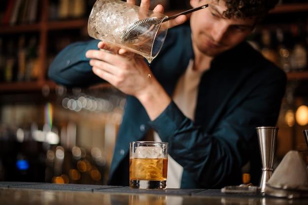 Barman finisce di preparare un cocktail alcolico old fashioned