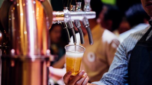 Barman o barista che versa una birra dal rubinetto della birra