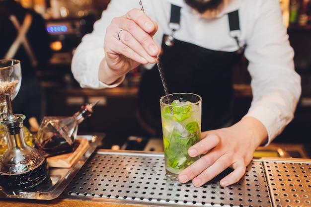 Barman prepara un cocktail al bar del ristorante.