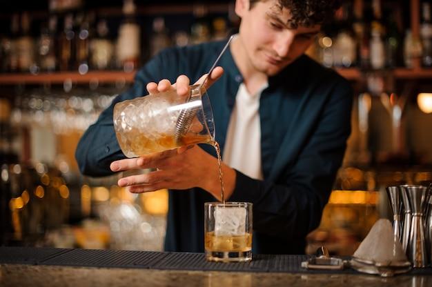 Barman prepara un cocktail alcolico vecchio stile, aggiungendo whisky al ghiaccio