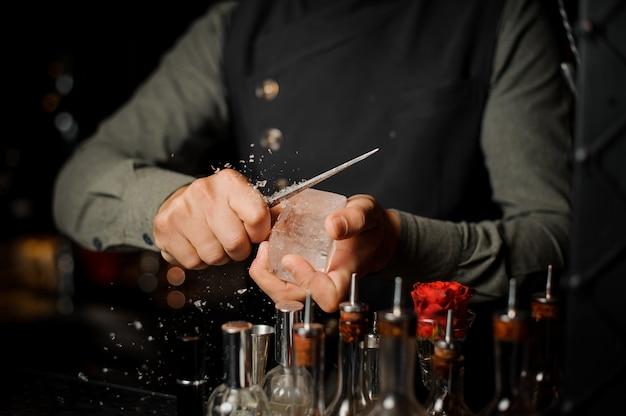 Barman prepara un grande pezzo rettangolare di ghiaccio
