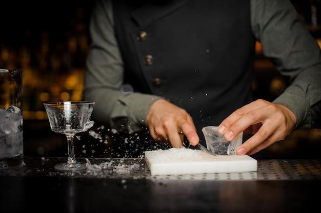 Barman prepara un grosso pezzo rettangolare di ghiaccio sulla scrivania di plastica