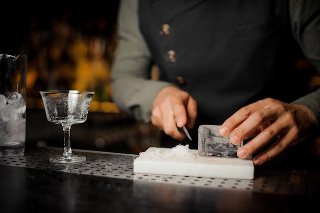 Barman prepara un pezzo di ghiaccio per fare il cocktail