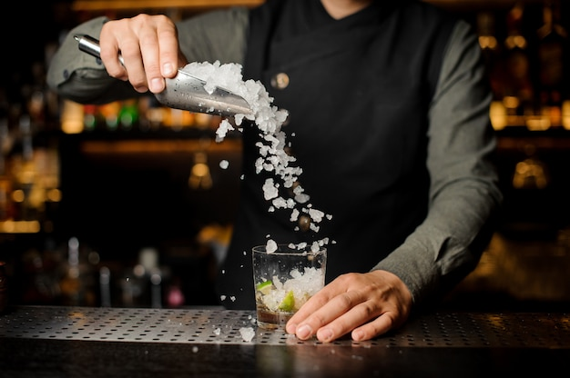 Barman puring ice nel bicchiere da cocktail