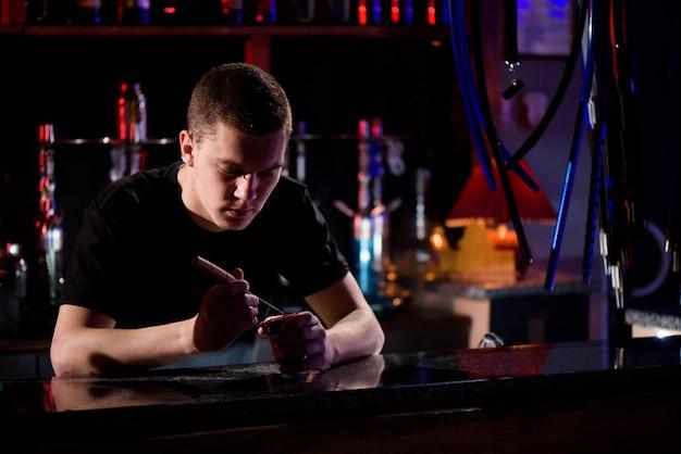 Barman riempie la ciotola in ceramica nera bruciata per narghilè fumando diversi tipi di tabacco.