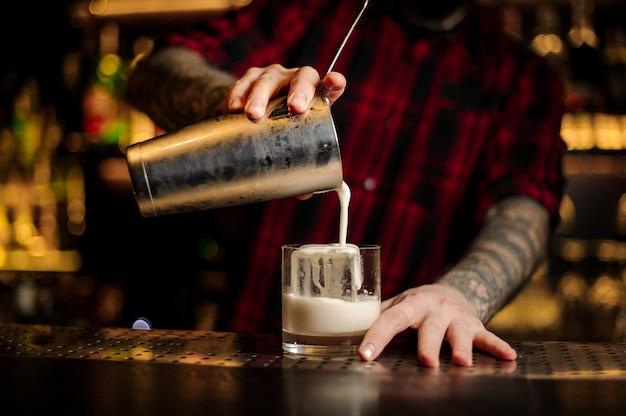 Barman versando fresca e densa bevanda alcolica cremosa in un bicchiere
