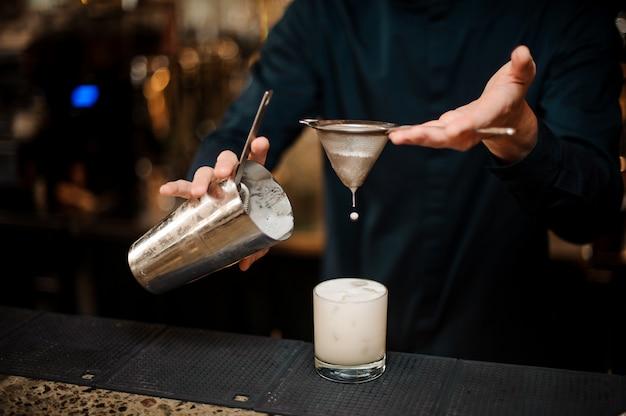 Barman versando un frappè alcolico in un bicchiere da cocktail