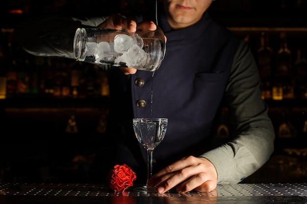 Barman versando una fresca bevanda alcolica in un bicchiere