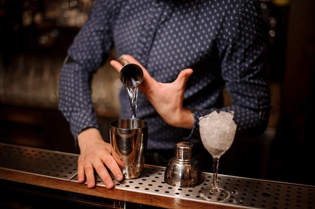 Barman versando una porzione di vodka nello shaker