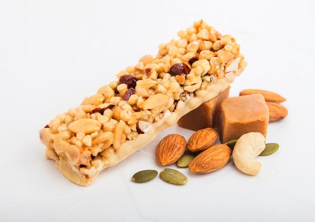 Barra di cereali biologici fatti in casa granola con noci e frutta secca su bianco con avena e grano crudo.