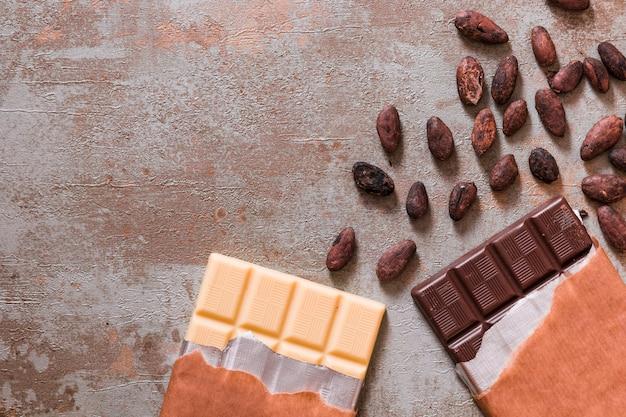 Barra di cioccolato bianco e scuro con fave di cacao crude su fondo rustico