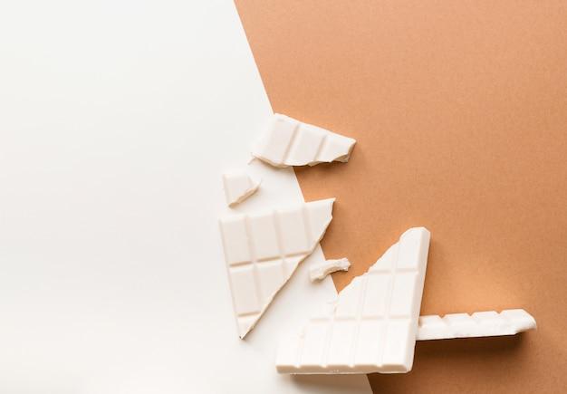 Barra di cioccolato bianco rotto contro doppio sfondo colorato