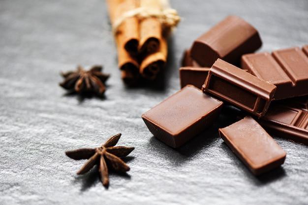 Barra di cioccolato e spezia sul dessert dolce della caramella del fondo scuro per lo spuntino