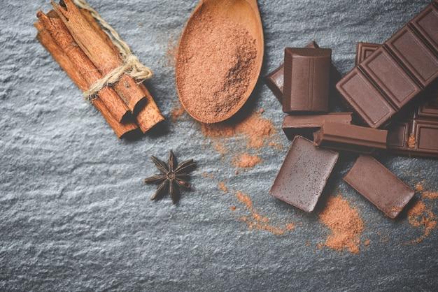 Barra di cioccolato e spezie su sfondo scuro cioccolato in polvere sul cucchiaio e pezzi di caramelle dessert dolce per merenda