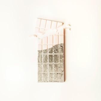 Barra di cioccolato rotta bianca in stagnola su fondo bianco