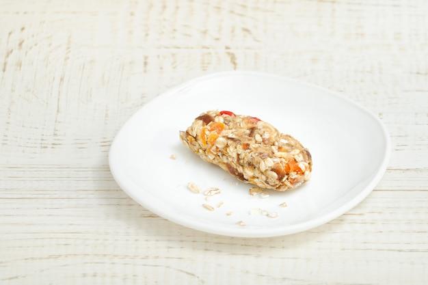 Barra di muesli su un piattino bianco. tavolo in legno bianco