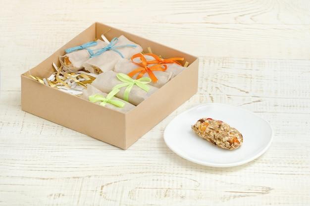 Barra di muesli su un piattino e scatole con barre. tavolo in legno bianco